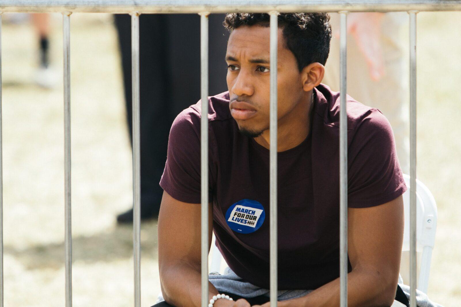 man sitting near metal fence