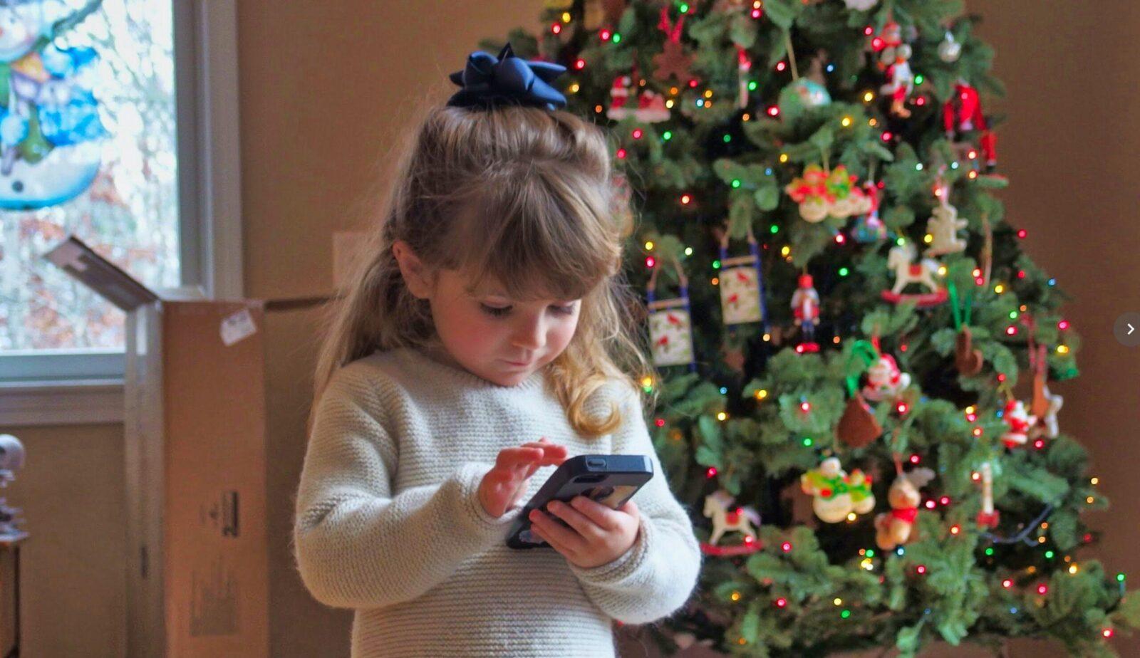 girl holding smartphone near Christmas tree