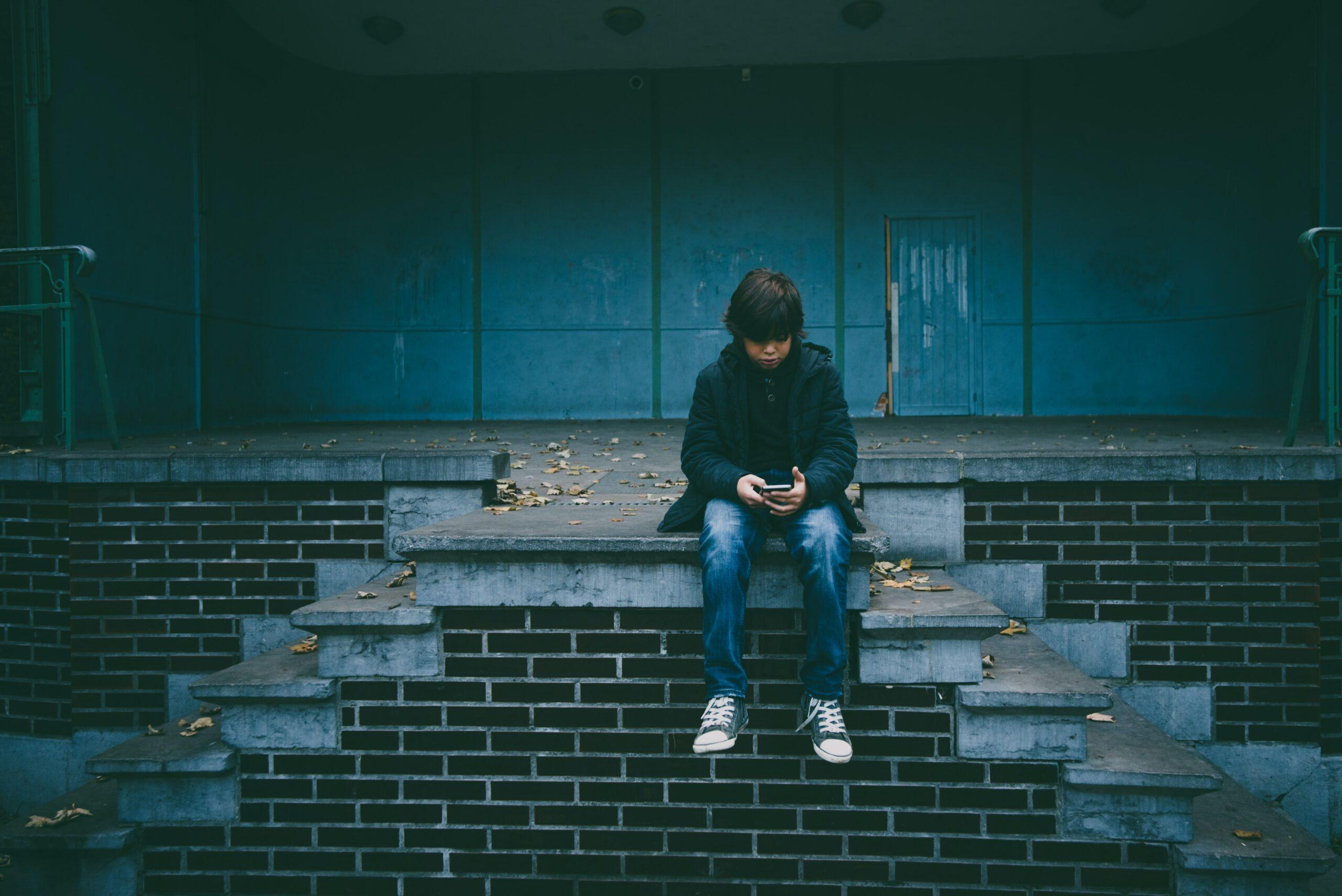 boy sitting on concrete stairs