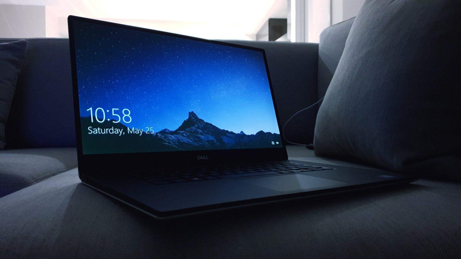 black Dell laptop on sofa