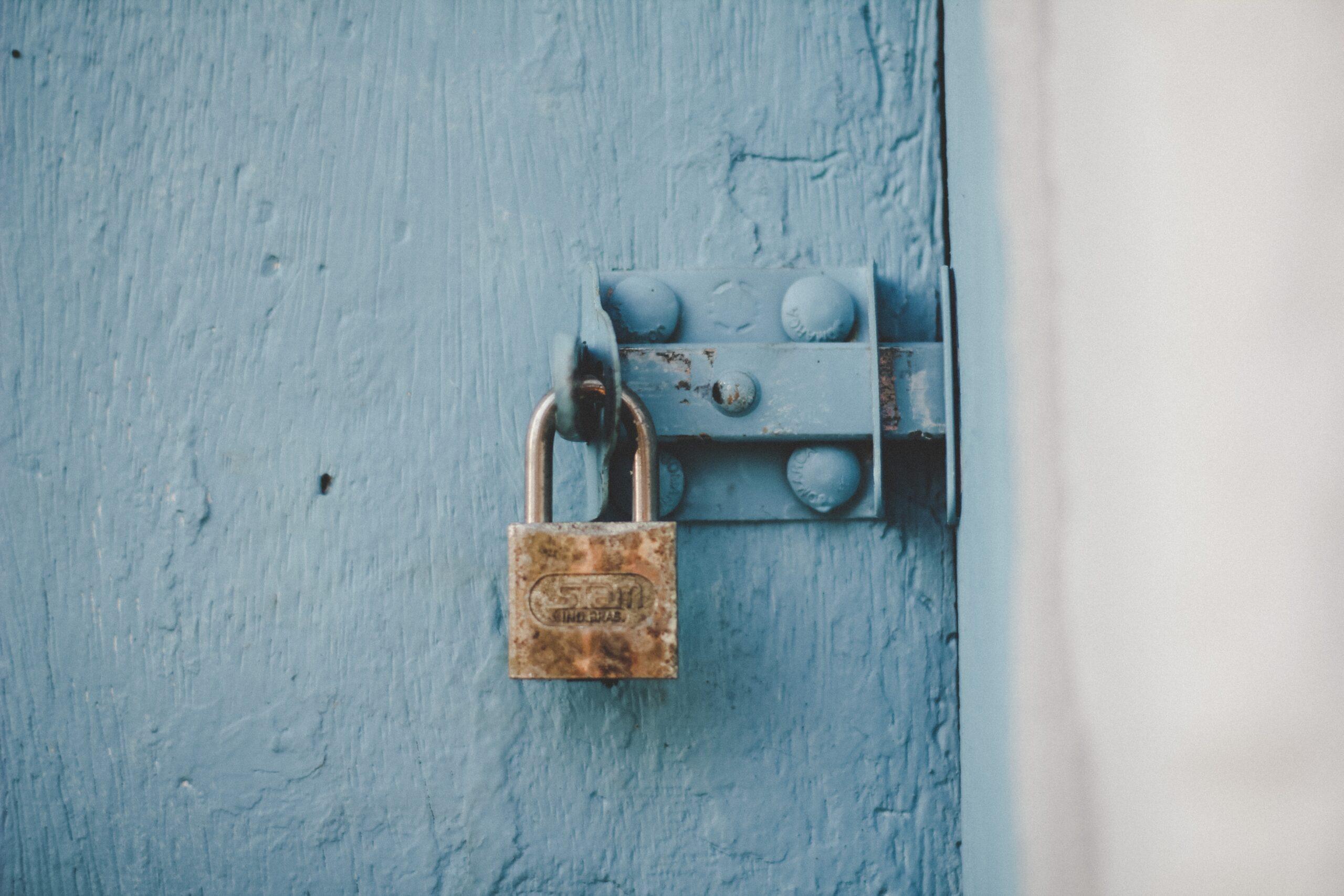 brown padlock on blue wooden door