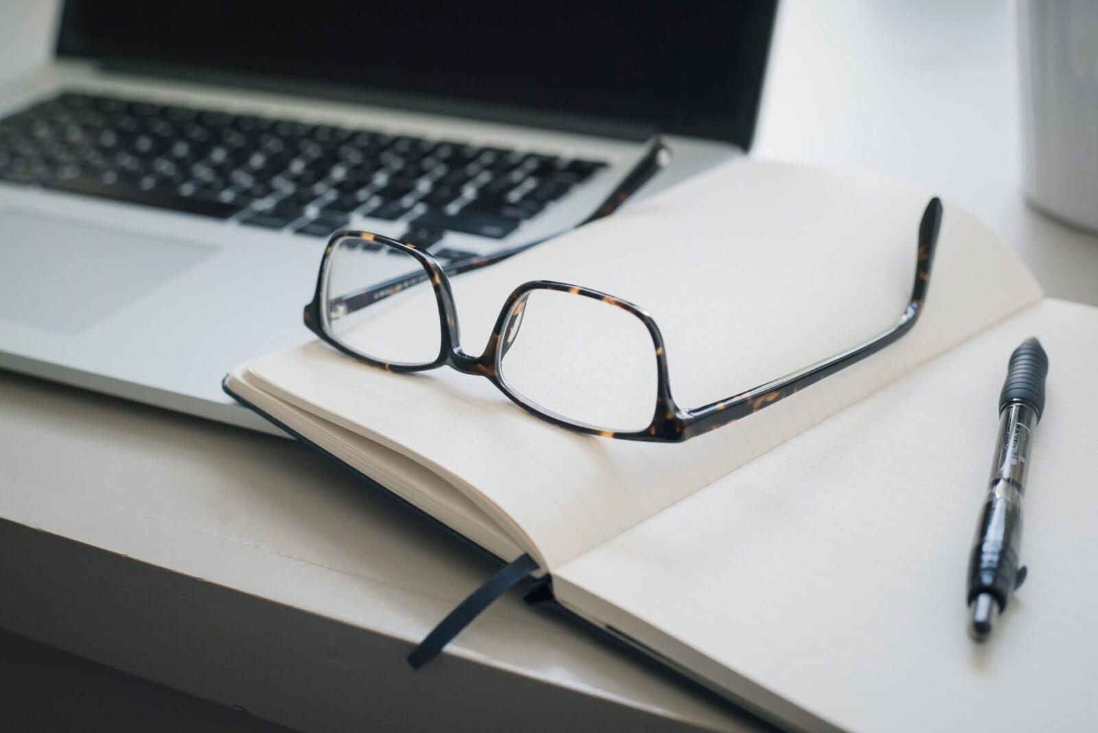 black framed eyeglasses and black pen