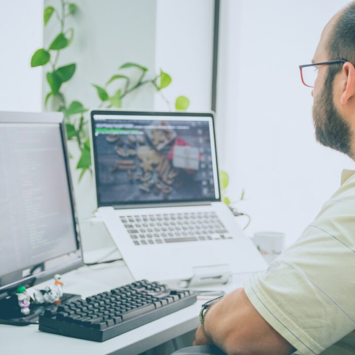 man sitting in front of computer monitor and laptop