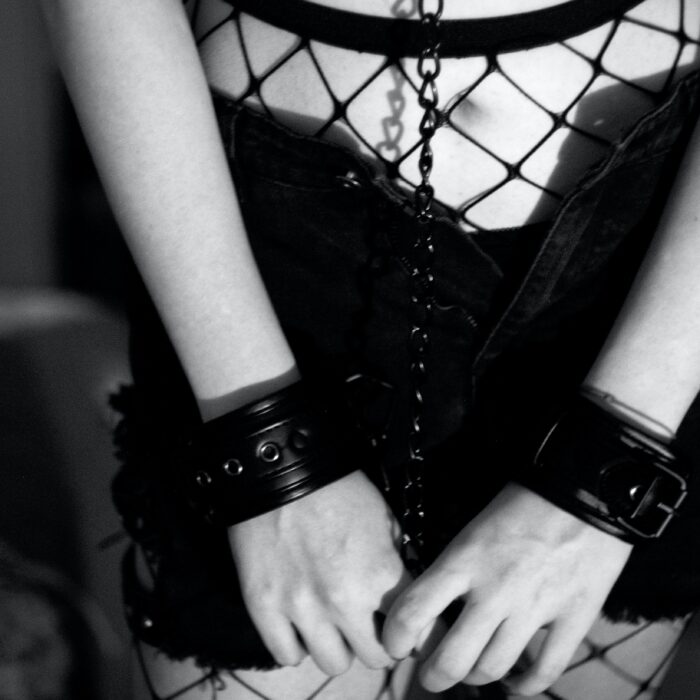 grayscale photo of woman wearing shorts and holding chain