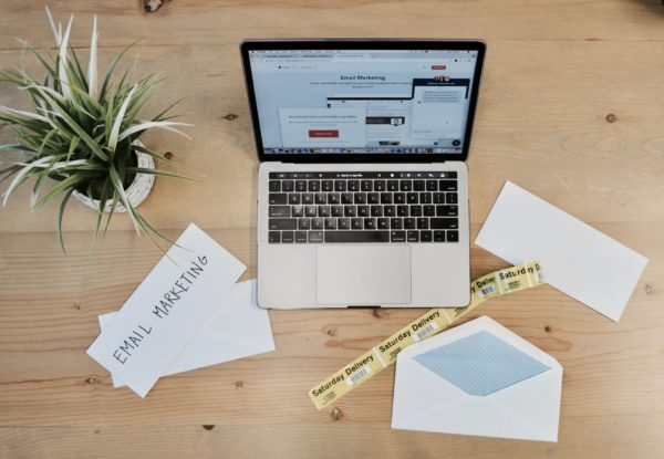 MacBook Pro beside white papers and plant