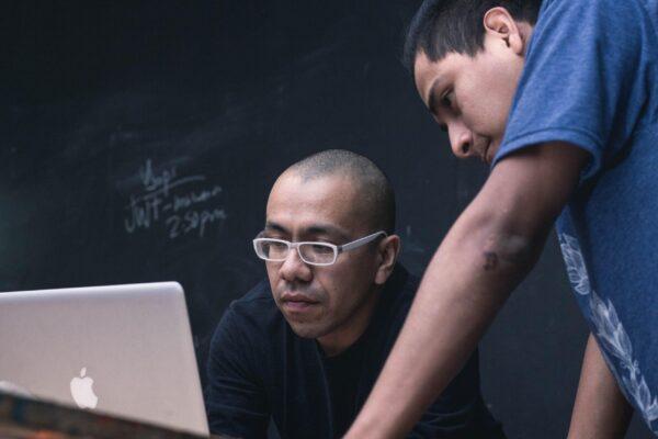 two men watching on silver MacBook