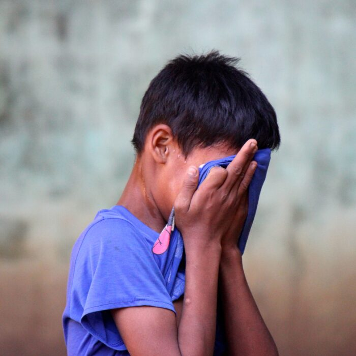 boy in blue shirt covering his face