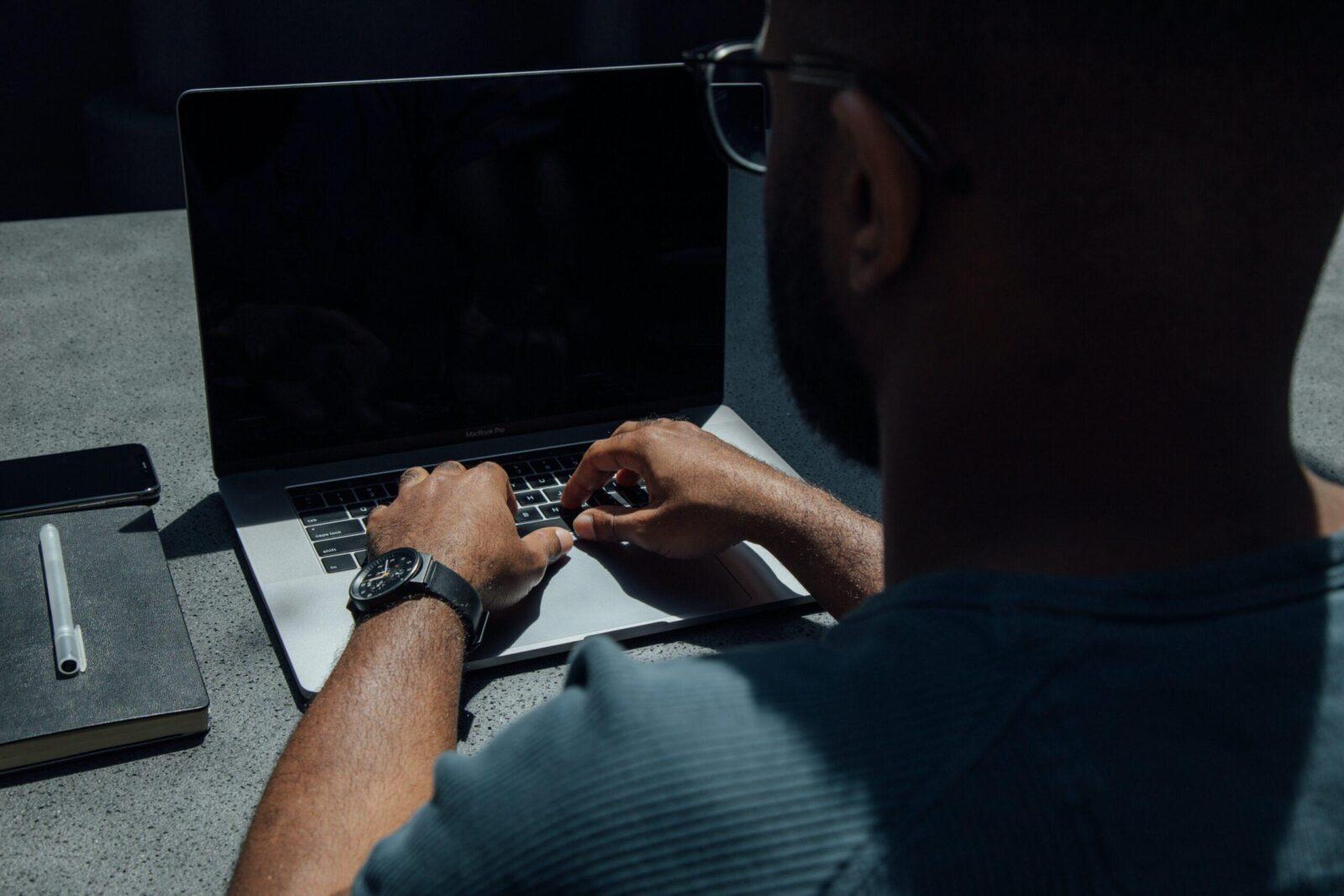 man using laptop computer on desk